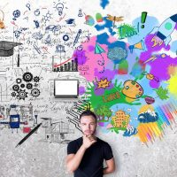 Creative and analytical thinking concept. Thoughtful man with colorful sketch on concrete background